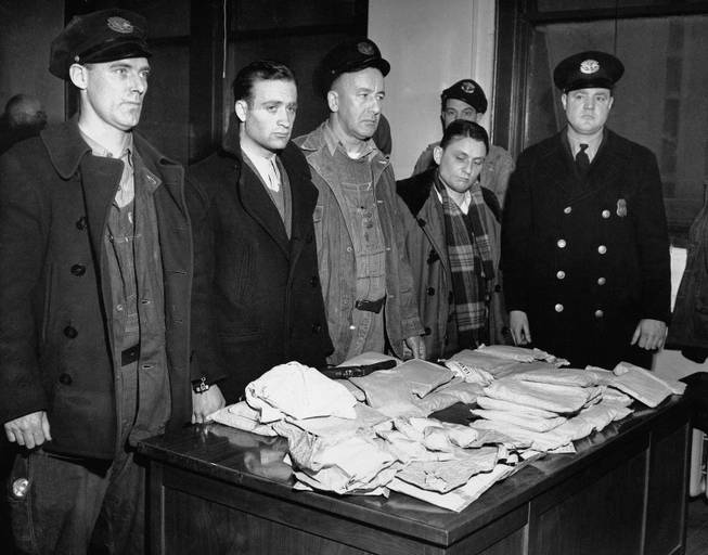 In this March 17, 1947 file photo, about 459 ounces of pure heroin valued at over one million dollars in the black market lies on table in Customs Enforcement Bureau in New York following seizure aboard the French freighter Saint Tropez after its arrival in New York City from Marseilles. Cesar Negro, Marseilles seaman, second from left, was arrested on charges of smuggling narcotics and Rene Bruchard, second from right, the ship's linen keeper, is being held for questioning. Port Patrol Officers Michael F. Munro, left; Arthur H. Cumming, center, and Lawrence F. Murray, right, are credited with discovering the heroin during a routine check of the seamen.