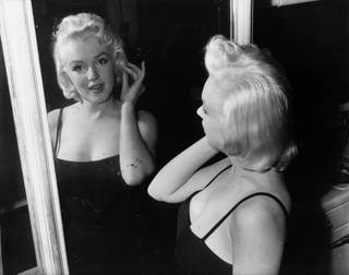 In conference - Actress Marilyn Monroe, film star turned business executive, checks her lines - all curves - in a mirror at the photographic studio of her business partner, Milton Greene, in New York Jan. 28, 1955.