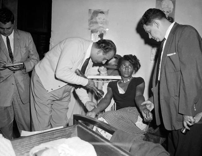 In this Sept. 22, 1957 file photo, police Detectives John Matassa, center and Sheldon Teller, right, examine the arms of a suspected narcotics addict and dealer in New York. Eric Schneider, a professor at the University of Pennsylvania said after World War II, heroin became a drug primarily used by blacks and Puerto Ricans in the Northeast and by Mexican Americans in the West. In the late 1960s, at the height of the hippie drug experimentation era, there was a resurgence of heroin use among young white people in the East Village and in San Franciscos Haight-Ashbury district.