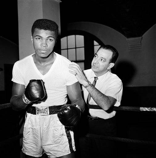 In this Feb. 8, 1962, file photo, a young Muhammad Ali is seen with his trainer Angelo Dundee at City Parks Gym in New York. The three-time heavyweight boxing champion will celebrate a milestone birthday Tuesday, Jan. 17, 2012, when he turns 70.