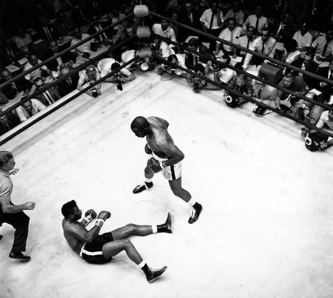 Floyd Patterson is on the ground after world heavyweight champion Sonny Liston staggers with a right then connects with a left for the knock out in Las Vegas, Nev. on July 22, 1963. This is the third in a three-picture sequence of the final knockout of Patterson in this match. (AP Photo)