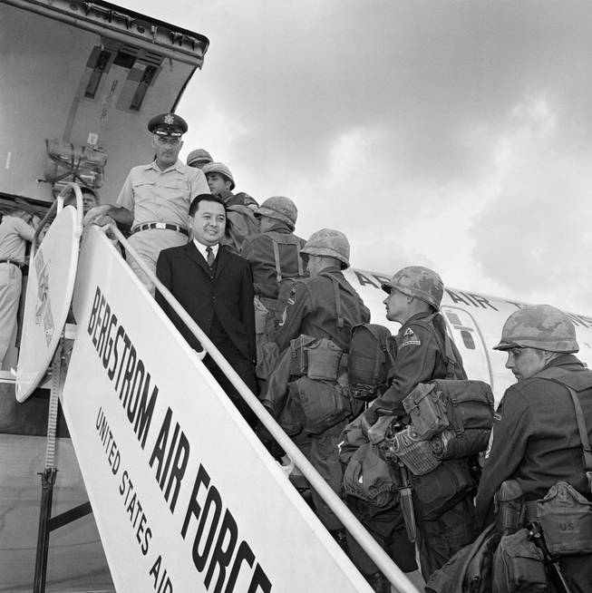 Sen. Daniel Inouye of Hawaii (dark suit) watches troops of the 2nd Armored Division, Fort Hood, Texas board a C135 jet transport plane on Oct. 23, 1963 at Bergstrom Air Force Base, Austin, Texas for a flight to Germany.   The senator, a member of the Senate Armed Services Committee accompanied them on their flight, a part of exercise big lift. Col. Frank R. Walsh, 340th group commander, stationed at Bergstrom AFB stands behind Sen. Inouye. (AP Photo)