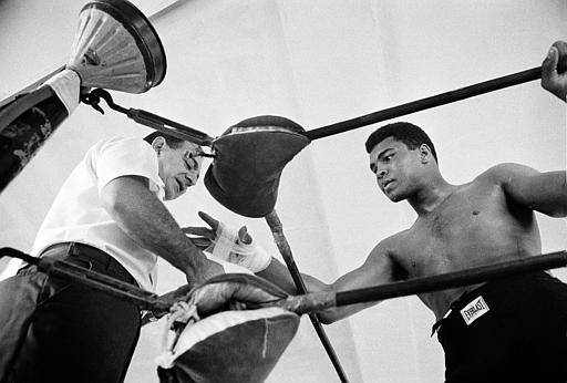 World heavyweight champion Muhammad Ali gets his hand taped by his manager Angelo Dundee before a sparring session in Miami Beach, Fla., on Oct. 13, 1966.