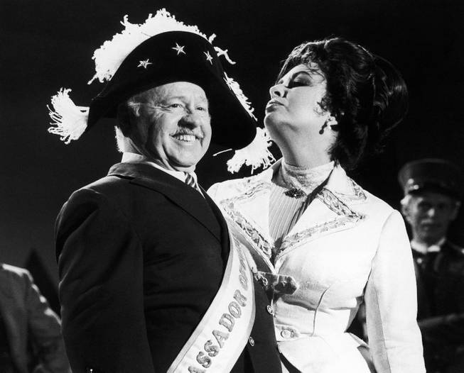 Veteran comic Mickey Rooney is a picture of poise in a Napoleonic era hat as he tapes an I love New York television commercial with British-American actress Elizabeth Taylor on Thursday, August 27, 1981 in New York, United States. Rooney is now starring in the review Sugar Babies on Broadway while Miss Taylor stars in Little Foxes.