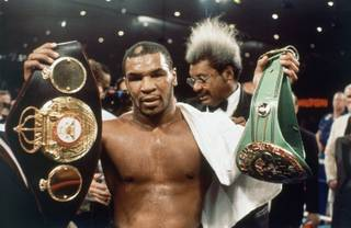 Boxer Mike Tyson holds double championship belts in Las Vegas, Saturday, March 7, 1987 after winning 12-round decision from James Smith to win the WB C/WBA Heavyweight Championship. (AP Photo)