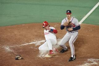 Phillies runner John Kruk scores in a wild pitch in the sixth inning as Atlanta Braves pitcher Steve Avery waits for the throw from catcher Damon Berryhill in game one of the league championship series at Veterans Stadium in Philadelphia, Wednesday, Oct. 6, 1993.