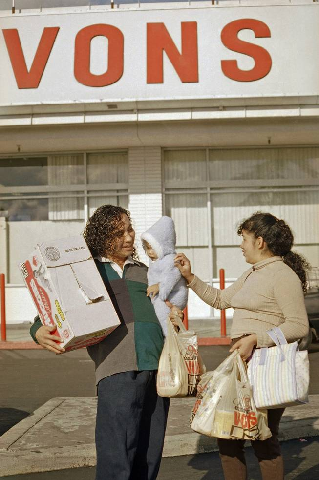 Raul Rios, left, and Rosalinda Ramirez attend to their 5-month-old daughter Angel Mayen, as they leave a Los Angeles Vons grocery store, Oct. 30, 1996. Safeway Inc. proposed a stock-swap merger with the Vons Companies Inc., to create a California grocery giant that would be the second-largest in North America.
