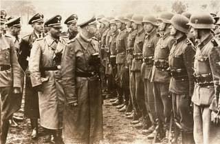The June 3, 1944 photo provided by the US Holocaust Memorial Museum shows Heinrich Himmler, centre,  SS Reichsfuehrer-SS, head of the Gestapo and the Waffen-SS, and Minister of the Interior of Nazi Germany from 1943 to 1945, as he reviews troops of the Galician SS-Volunteer Infantry Division.   Michael Karkoc  a top commander whose Nazi SS-led unit is blamed for burning villages filled with women and children lied to American immigration officials to get into the United States and has been living in Minnesota since shortly after World War II, according to evidence uncovered by The Associated Press. Michael Karkoc became a member of the Galician division after the Ukrainian Self Defense Legion was incorporated into it near the end of the war.