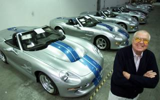 Automotive legend Carroll Shelby poses in front of his Shelby Series 1 sports cars at his plant in Las Vegas, Friday, Oct. 27, 2000. The Texas-born Shelby is mass producing a new generation of roadsters not in Detroit, but in the desert outside Las Vegas. The $174,975 Shelby Series 1 sports cars are 21st-century clones of his 1965 Cobra. And unlike his earlier model, the Shelby Series 1 has creature comforts like roll-up windows and air conditioning.
