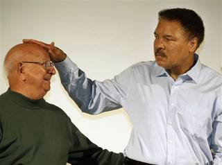 FILE - In this Oct. 9, 2003, file photo, boxing great Muhammad Ali touches the head of his former coach Angelo Dundee at the Book Fair in Frankfurt, Germany. Dundee, the trainer who helped groom Ali and Sugar Ray Leonard into world champions and became one of boxing's most recognizable figures, died Wednesday, Feb. 1, 2012. He was 90. (AP Photo/Michael Probst, File)