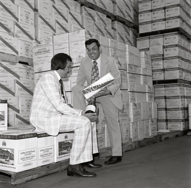 Larry Ruvo, left, and Jerry Vallen look over a bottle of wine at the SWS warehouse for the first ever UNLVino event in that took place in 1974.