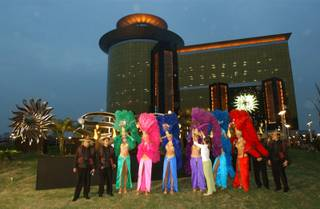 Las Vegas dancing girls adjust their costums as they are joined by employees of the Las Vegas Sands casino dressed as old style Chinese tea traders as they get ready to pose for a picture in front the Las Vegas Sands casino in the former Portuguese enclave of Macau, on Monday, May 17, 2004, one day before it is due to open.