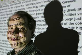 Author and inventor Ray Kurzweil, 56, appears in front of words projected on a screen from his Internet site in his office, in Wellesley, Mass., Jan. 12, 2005.