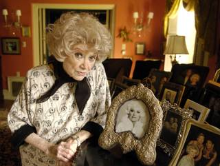 Phyllis Diller poses with her photos at her home in the Brentwood section of Los Angeles, Friday, March 11, 2005. Female standup comics had never made the big-time, but Diller beat the odds, paving the way for Lily Tomlin, Rosanne, Ellen DeGeneres and others to follow. Diller relates her saga in her new memoir,