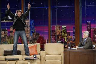 In this photo released by NBC, Tom Cruise jumps onto the sofa after greeting host Jay Leno on the set of
