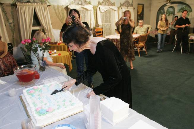 "Marta Becket cuts a celebratory cake after performing her one-woman show ""Masquerade"" to open the 2005-2006 season at the Amargosa Opera House in Death Valley Junction Oct. 1st, 2005."