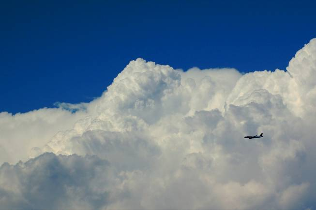 A plane landing at McCarran International Airport from the east, passes a large cloud during the monsoon season.