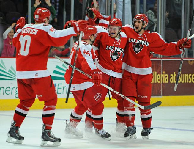 Las Vegas Wranglers come together to celebrate a tie-breaking goal scored by Matt Tassone (far right) with under a minute left to play in the third period against the Alaska Aces on Saturday night.