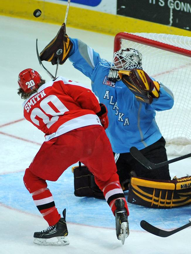 Alaska Aces goaltender Aaron Crandal deflects a shot with his blocker as Las Vegas Wranglers forward Robbie Smith swings his stick at the fluttering puck during the second period of play on Saturday night.