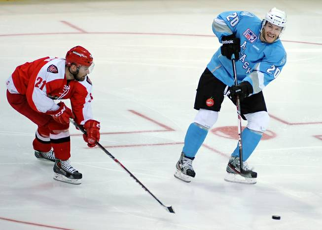 Alaska Aces defenseman Corey Syvret lofts the puck to a teammate as Wranglers defenseman Greg Coburn persues the play during an ECHL game at the Orleans Arena on Saturday night.