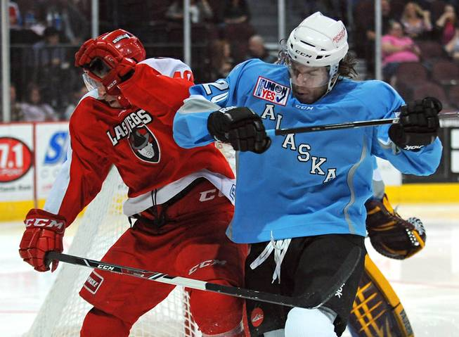 Alaska Aces defenseman Corey Syvret (right) collides with Wranglers center Geoff Paukovich during the third period of play on Saturday night.