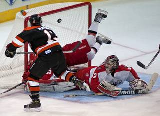 Las Vegas Wranglers goaltender Travis Fullerton looks towards the back of the net as Fort Wayne Komets right winger Brandon Marino (13) roofs the puck for a third period goal to give the Komets a 4-1 lead.