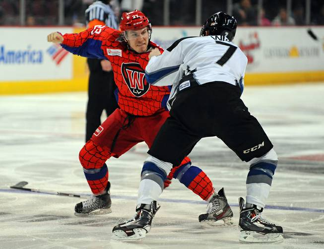 Chad Nehring (23) fights Mitch Wahl near the start of the third period of play between the Las Vegas Wranglers and the Idaho Steelheads on Saturday night.