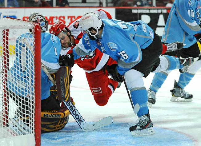 Las Vegas Wranglers center John Armstrong (91) is thrown down in the Aces crease by Alaska defenseman Sean Curry during the third period on Sunday afternoon.