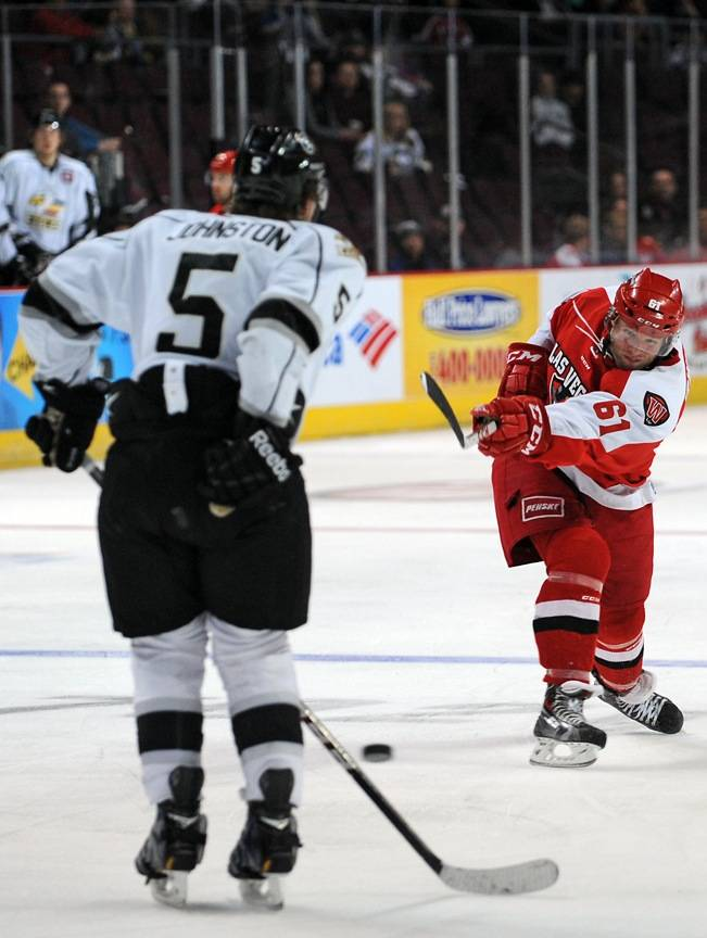 Wranglers forward Geoff Irwin (61) fires a shot towards Colorado Eagles defenseman Daniel Johnston (5) during the second period of play on Tuesday night at the Orleans Arena.