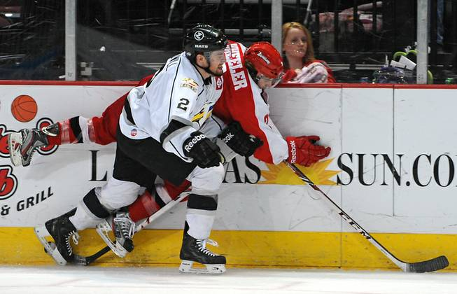 Colorado Eagles defenseman Arthur Bidwill (2) checks Wranglers defenseman Nick Wheeler into the boards during a game at the Orleans Arena on Wednesday night.