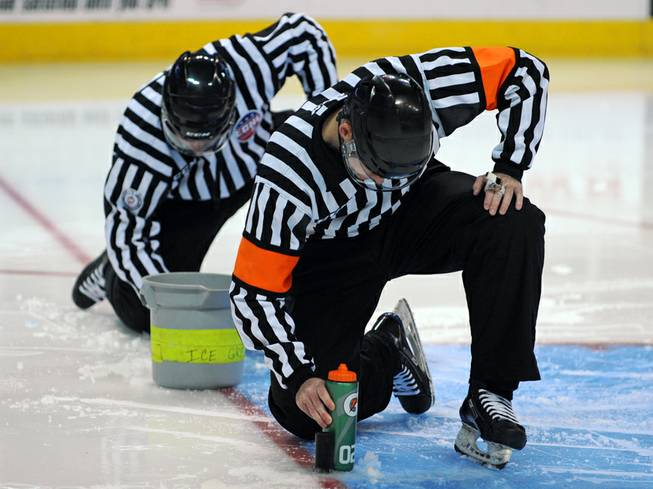 ECHL referee Ryan Murphy and linesman Wally Lacroix help make repairs to the ice surface near where the goal pegs are inserted before the start of the third period between the Wranglers and the Colorado Eagles on Wednesday night at the Orleans Arena.