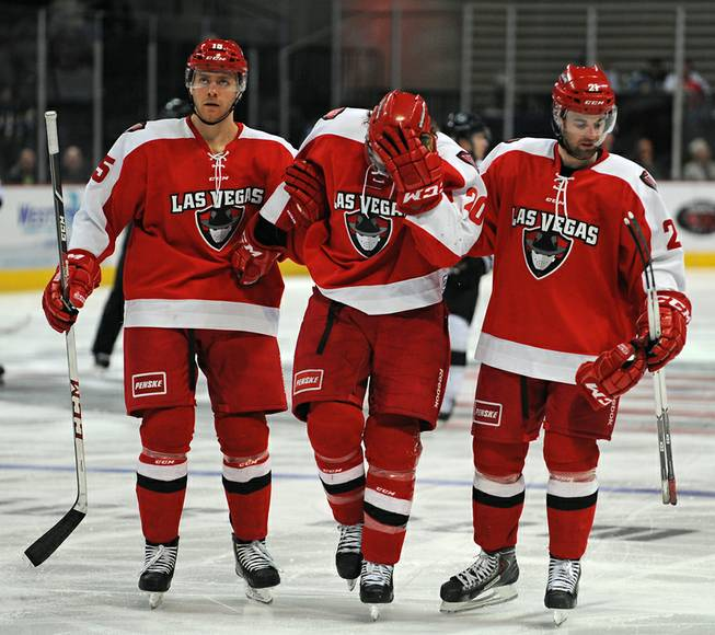 Las Vegas Wranglers foward Robert Smith (center) is helped off the ice by teammates Brendan Rempel, left, and Greg Coburn after suffering a knee injury after a collision with an Eagle player during the third period of play against the Colorado Eagles on Wednesday night.