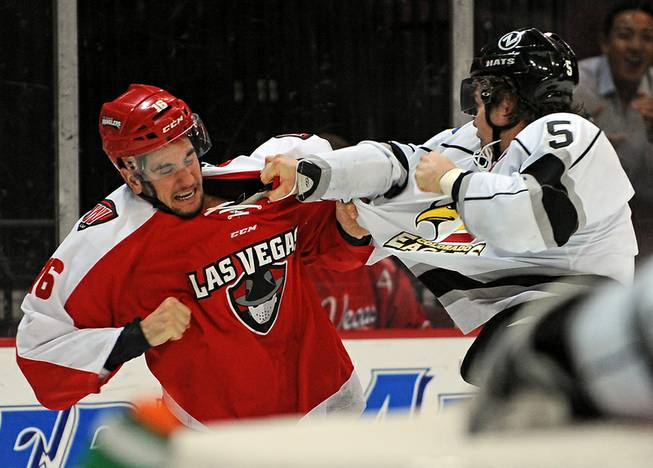 Las Vegas Wranglers forward Matt Tassone (16) fights with Colorado Eagles defenseman Daniel Johnston during the third period of play on Wednesday night.