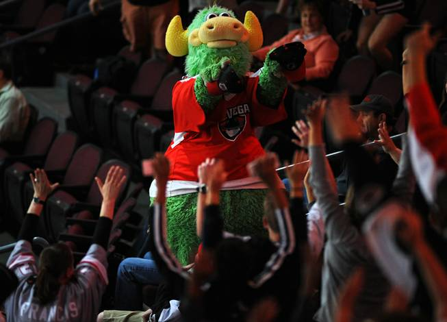 "Las Vegas Wranglers mascot ""The Duke"" passes out hats to cheering fans during a stoppage in play between the Wranglers and the Bakersfield Condors on ""Fan Appreciation Night"" on Tuesday night."
