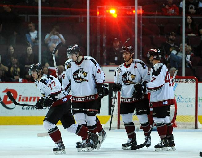 The red goal light fllashes as Bakersfield Condors players skate toward their bench to celebrate after scoring a goal against the Las Vegas Wranglers on Tuesday night.