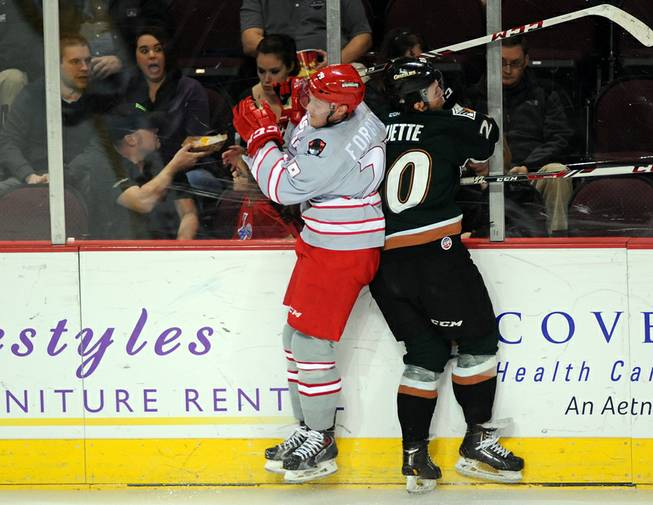 Las Vegas Wranglers defenseman Ryan Forgaard, left, turns to hit Utah Grizzlies forward Danick Paquette against the glass during the second period on Friday night at the Orleans Arena.