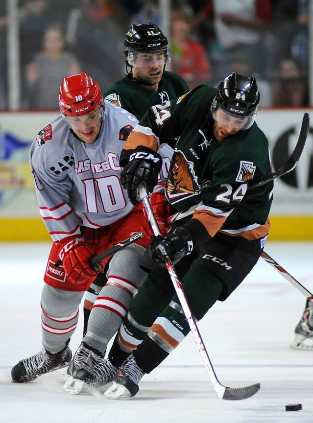 Las Vegas Wranglers captain Geoff Paukovich, left, battles for control of the puck with Utah Grizzlies defenseman Martin Lee during the third period of play on Friday night.