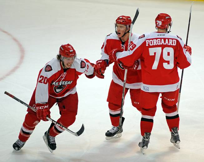 Las Vegas Wranglers forward Adam Hughesman, center, celebrates with Robbie Smith, left, after assisting on a Smith goal against the Colorado Eagles on Tuesday night. At right is Wranglers defenseman Ryan Forgaard.