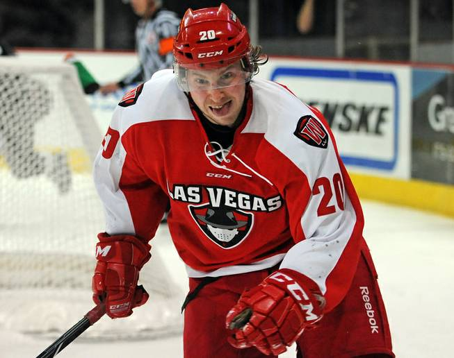 Las Vegas Wranglers forward Robbie Smith keeps his eyes on a puck as it bounces along the boards during an ECHL game against the Colorado Eagles on Tuesday night.