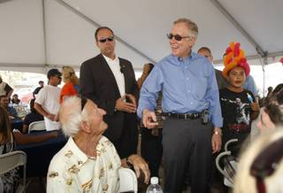 Senate Majority Leader Harry Reid, center, smiles as he chats with retired union carpenter Damon Bingle, left, who recently turned 90 years old, during an early Labor Day celebration for union members and their families in downtown Las Vegas on Thursday.
