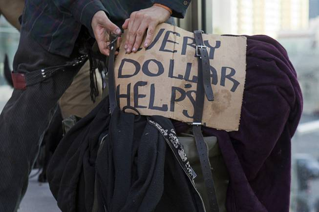 A panhandler packs up to leave after soliciting money with a dog on a pedestrian overpass near Planet Hollywood Friday, Dec. 30, 2011. A proposed county ordinance would ban the use of dogs and other animals by people soliciting money on the Strip.