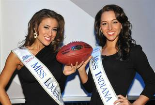 Miss Louisiana Katherine Putnam and Miss Indiana Nicole Pollard pose for photos with an official Super Bowl XLIV game ball at Planet Hollywood on Jan. 25, 2010.