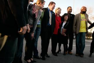 Hillary Clinton poses for a photo with her Nevada staff after a news conference in a parking lot on her way out of town after her Nevada Democratic caucus win Saturday.