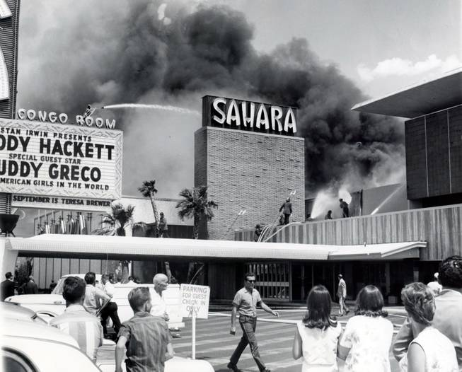 Guests hang back as firefighters work to put out the blaze at the Sahara hotel in 1964. This fire is a precursor to the devastating MGM Grand fire in 1980.