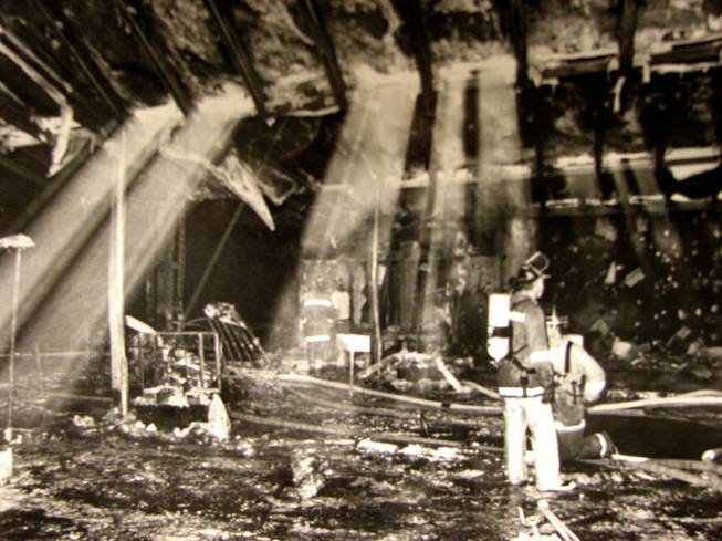 Light cascades down on Firefighters as they sift through the rubble of the MGM Grand Hotel's lobby. The fire began Nov. 21, 1980 on the Casino floor, but quickly spread to the lobby and main entrance of the hotel.