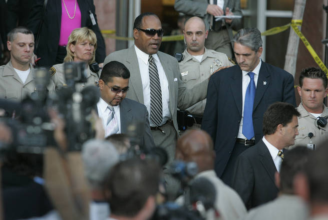 O.J. Simpson walks out of the Clark County Regional Justice Center Wednesday, April, 9, 2008,  after learning he and two co-defendants will go to trial on armed robbery and kidnapping charges.