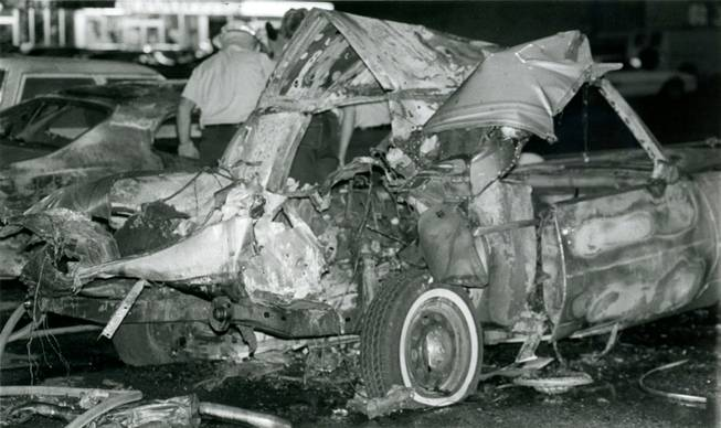 "Investigators examine the area surrounding the twisted remnants of Frank ""Lefty"" Rosenthal's car after a bomb destroyed the vehicle on Oct. 4, 1982. A metal plate directly underneath the driver's seat of the Cadillac diverted the explosion away from Rosenthal, saving his life."