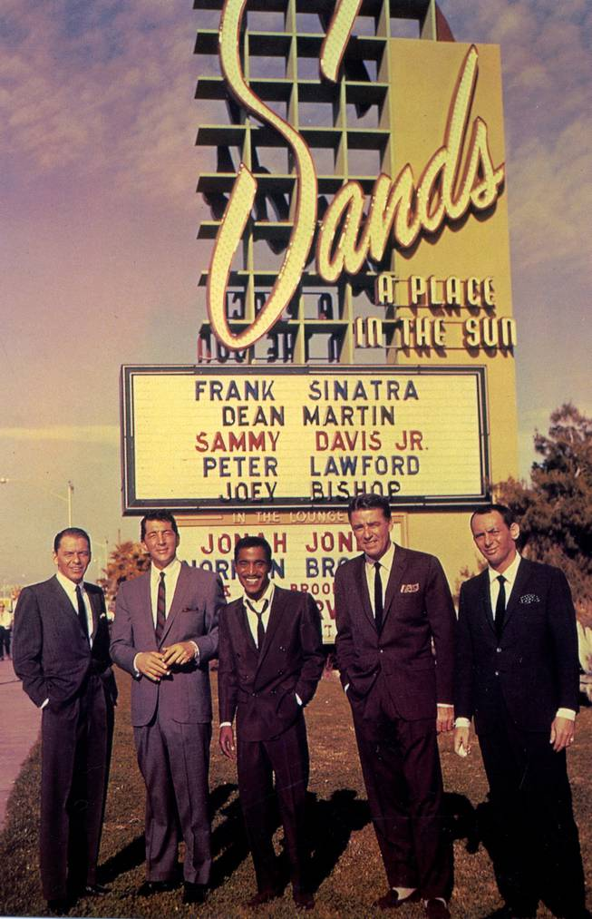 A postcard shows the Rat Pack (from left Frank Sinatra, Dean Martin, Sammy Davis Jr., Peter Lawford and Joey Bishop) posing in front of a Sands Hotel marquee bearing their names. Their performances at the Sands during the 60s marked the golden age of the group.