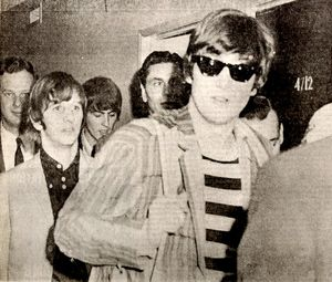 The Beatles are ushered to their room at the Sahara hotel before performing at the Las Vegas Convention Center on Aug. 20, 1964. John Lennon dons sunglasses and stands in front, with Ringo Starr on the left and George Harrison, looking down behind Ringo.