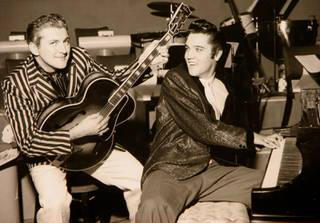 Liberace and Elvis Presley trade jackets and instruments in an impromptu jam session at the Riviera on Nov. 14, 1956.